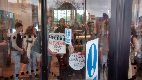 The students make their point inside the glass entrance doors.
